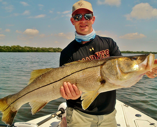 Young man holding large snook caught on a fishing charter with Florida Inshore Xtream Fishing Charters, Boca Grande, Englewood and Pine Island Sound