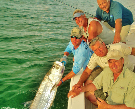 A charter group holding a huge tarpon caught with Capt. Jesse in Boca Grande.