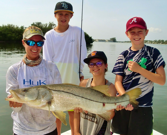 A group of kids holding a large snook caught with Capt. Kelly around Pine Island Sound.